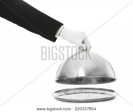 Waiter's hand holding cloche over tray against white background