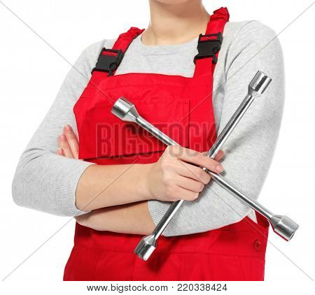 Female auto mechanic with lug wrench on white background, closeup
