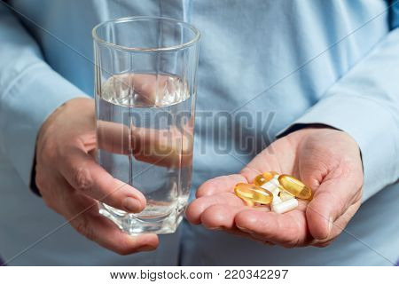 Woman take in the hand variety medication pills, yellow capsules of omega 3, glucosamine and calcium dietary supplements in the palm hand.