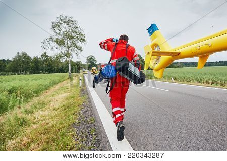 Doctor with defibrillator and other equipment running from helicopter. Teams of the Emergency medical service are responding to an traffic accident.