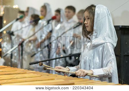 girl is playing a xylophone. White clothes, choir
