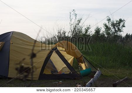 Touristic tent in a forest. Tent camping in the woods. Tourists camped in the woods on the shore of the lake on the hillside