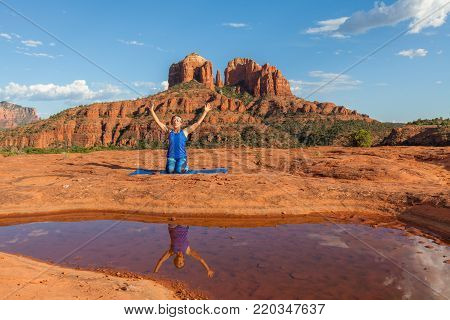 a woman practicing yoga near scenic cathedral rock sedona arizona
