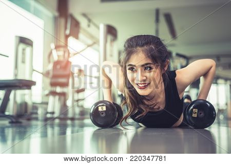 Asian young woman doing push ups with dumbbell on floor in fitness gym and equipment background. Workout and Sport Exercise concept. Healthy and Happiness concept. Beauty and Body build up theme.