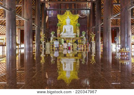 Buriram ,Thailand - December 28 , 2017 : White jade Buddha statue in Pa Lahan Sai temple with reflection