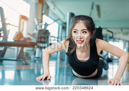 Asian woman fitness girl do pushing ups at fitness gym. Healthcare and Healthy concept. Training and Body build up theme. Strength and Beauty concept