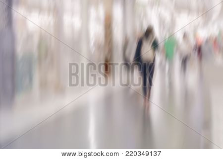 Abstract defocused motion blurred young people walking in shopping center. Unrecognizable figures of girls, urban lifestyle concept. For background , backdrop, substrate, composition use