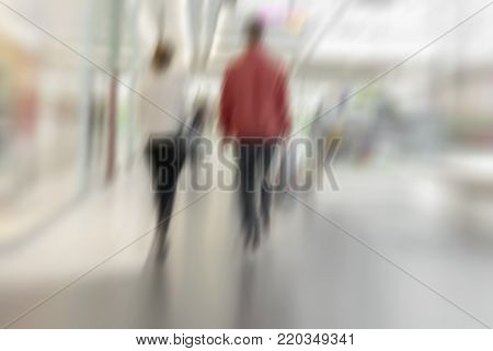 Abstract defocused motion blurred unrecognizable couple, two young people in shopping center, urban lifestyle and shopping concept, background