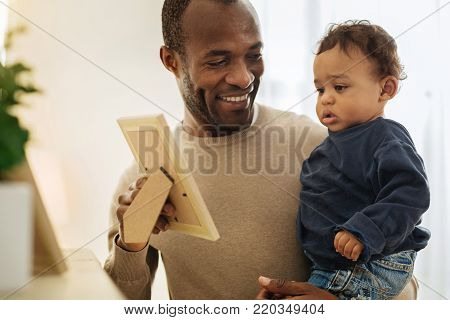 Happy fatherhood. Happy dark-haired afro-american man smiling and showing photos to his son while holding him in his arms poster
