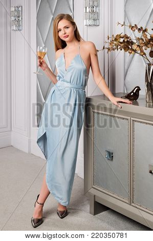 Elegant blonde lady with glass of wine in restaurant. Beautiful sexy young woman with long hair perfect body and pretty face make-up wearing blue evening dress drinking alcohol in luxury interior