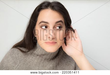 Series of  portraits of a beautiful woman listening with her hand to her ear isolated on white background with copy space