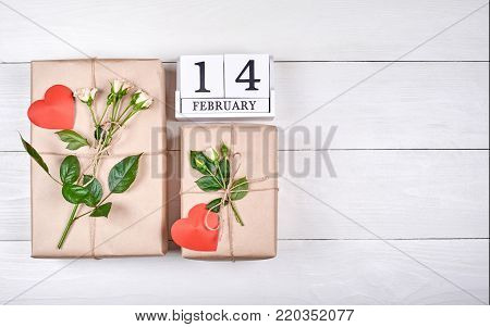 Top view of block calendar with february 14 and gift boxes wrapped in kraft with fresh roses and red hearts on wooden table, copy space. Sale, shopping. Greeting card for Valentines Day, flat lay