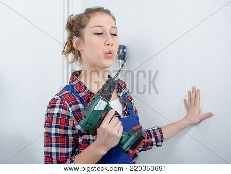 pretty young smiling woman holding cordless drill