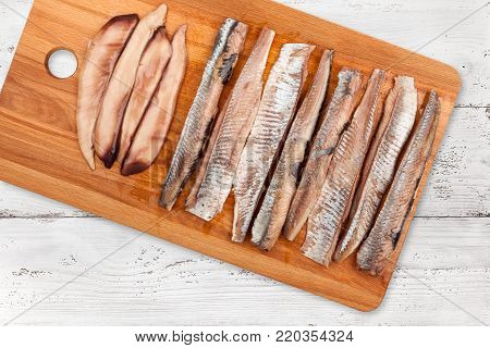 Wooden cutting board with a herring fillet on light wooden background, top view