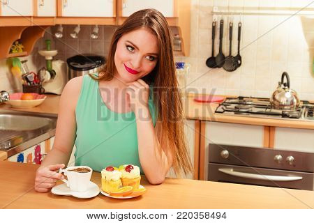 Woman drinking coffee and having breakfast. Glutton girl sitting in kitchen with hot beverage, delicious gourmet sweet cream cake cupcake and orange. Appetite and gluttony concept.