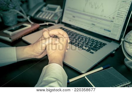 Business man is praying while trading stock market on computer