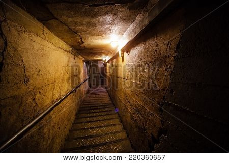 Dark corridor of old underground Soviet military bunker under artillery fortification, Sevastopol, Crimea. Staircase goes down