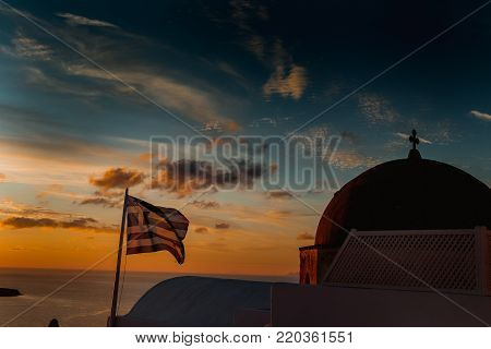 Santorini sky in Sunset with Greece flag and blue dome of church in Oia, Santorini