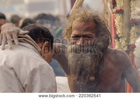 BABUGHAT, KOLKATA, WEST BENGAL / INDIA - 11TH JANUARY 2015 : Hindu Sadhu with white ash applied on body and face, blessing Indian devotee man.