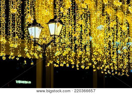 Metal lantern on background of shiny neon garland, night, city street. Fall and fest backdrop. Festive occasions concept, holiday, Christmas, New Year backdrop