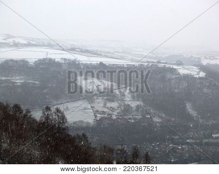 snow falling in a yorkshire dales landscape with winter trees and farms visible on the hills with bushes and heather in the foreground