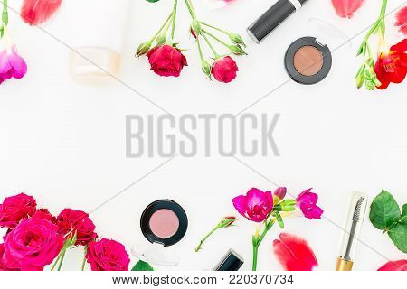 Flat lay, top view. Feminine desk workspace with cosmetics, lipstick, cream and roses on white background.
