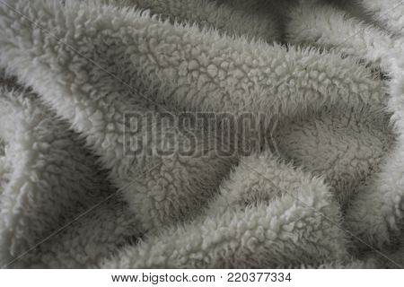 Folds are created in this fuzzy, soft and warm beige blanket.