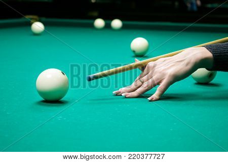 Female hand holds a cue for striking the white cue ball. Woman playing billiards. Russian pyramid (Russian billiard, pyramid billiards), cue sport.