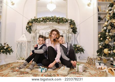 Happy mother and beautiful woman posing on camera with two children, twin boys. Women and children hold gift boxes, shake gifts, smile and bring them closer to lens, sitting on floor, on beautiful carpet in bright Christmas-decorated living room with tall
