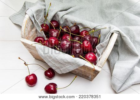 Wooden basket full of raw red cherry berries wrapped in a grey cotton cloth at white wooden background