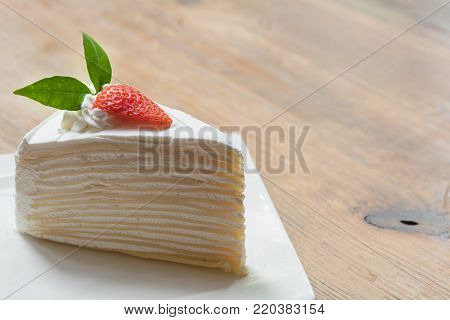 Strawberry crape cake in white plate with closeup view on wooden and ready to served in the morning.