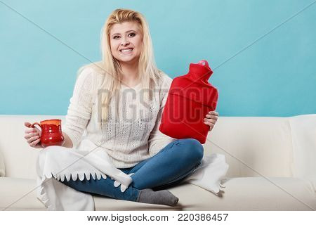 Happy woman showing ways to get rid of fever holding hot water bottle and hot drink in mug sitting, relaxing on couch.