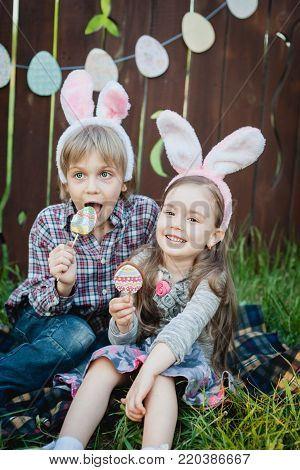 Little Girl And Boy Eat A Gingerbread Cookie In The Shape Of The Easter Egg.