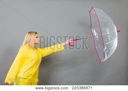 Rainy autumn day accessories ideas concept. Serious woman holding opening clear transparent umbrella fighting with wind.