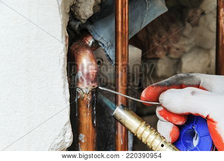 A worker is using the gas burner and the solder for soldering copper pipes.