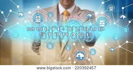 Unrecognizable enterprise solution manager is activating MULTI-CLOUD STORAGE onscreen. IT concept for hybrid delivery model of flexible data storage across multiple clouds via computing network.