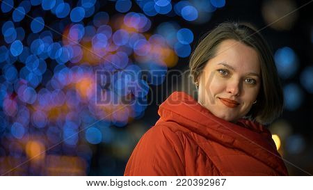 Woman is smiling and looking at camera. There is free space for text or any other design needs in the left part of the image. She tilted her head a little bit. Photo was taken on a street.
