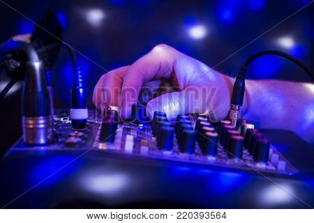 DJ mixing party music on blue background with lights.