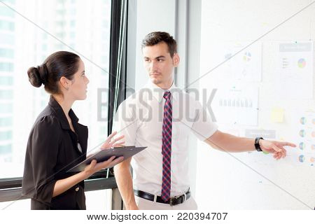 young businessman pointing towards graph and businesswoman holding clipboard with present profit while giving presentation in office, teamwork concept.