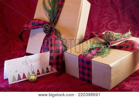 holiday gifts wrapped with ribbons in holiday theme decor and greeting card with ornament