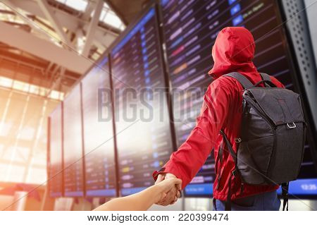 Young man Man holding hand of wife following himwith backpack and carry on luggage in international airport, near flight information board.Travel Concept.