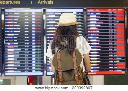 Young woman with backpack and carry on luggage in international airport, near flight information board.Travel Concept.