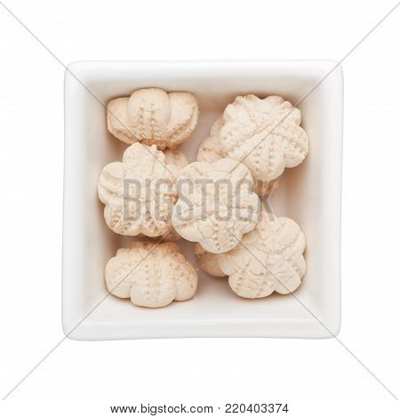 Kueh bangkit pastry in a square bowl isolated on white background