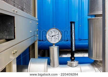The pressure gage and thermometer in water cold pipe on air condition system