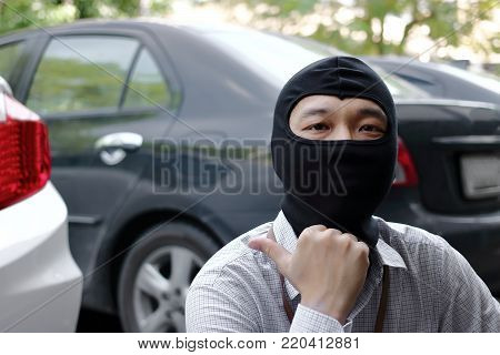Masked thief in action before burglary. Car thief criminal concept.