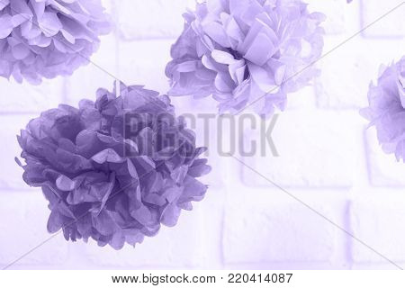 Paper flowers at the baby shower party.  Party decoration and celebration concept. Festive party background. Horizontal, white brick background. Ultra violet tone, color of the year 2018