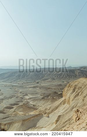 View on desert sunny land near dead sea in Israel. Valley of sand, mountains and stones in hot middle east tourism place. Scenic outdoor infinity on wild land. Summer heat and nobody on photo