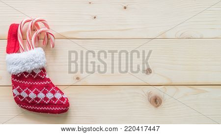 Christmas gift background with red baby stocking (sock) candy cane present on white pine wood background for X'mas winter holiday backdrop design decoration