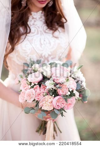 Young bride holding wedding bouquet with roses outdoors. Wedding day. Celebration. 20s. poster