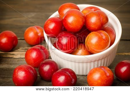 Plum fruit (Julee) in white bowl on wooden background